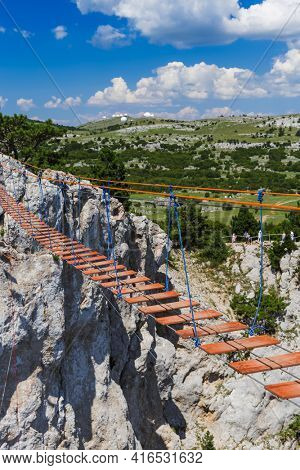 Suspension rope ladder in mountains over the chasm - travel background