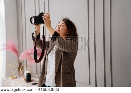 A Brunette Woman Working Photographer. Photo Shoot In A Photo Studio. Backstage