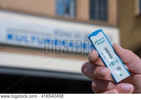 Berlin, Germany - April 11, 2021: Hand Hold Express Covid-19 Test In Front Of Cafe In Kulturbrauerei