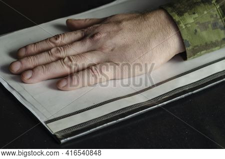 The Hand Of A Adult Man In A Military Uniform Lies On Top Of A File Folder Of Documents. A Middle-ag