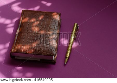 Light And Shadow Composition With A Closed Diary On A Pink Table. A Notebook In A Brown Cover. Gold-