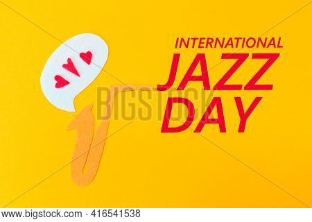 A Cutted Out Of Felt Saxophone From Which Hearts Flew Out, On A Yellow Background. Flat Lay. Interna