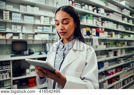 Young Female Pharmacist Working Using Digital Tablet Standing In Chemist Wearing Labcoat