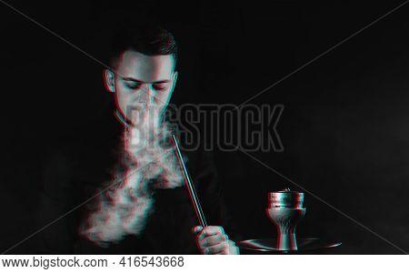 Male Smoker Smokes A Hookah And Lets Out A Cloud Of Smoke