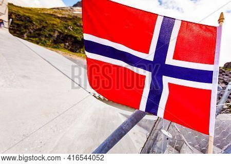 Norwegian Flag Against Utsikten Viewpoint At Gaularfjellet. Tourist Attraction. Scenic Route In Norw