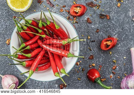 Red Chilli Pods In Bowl With Garlic And Lemon Slices Lie On Concrete Surface, Top View