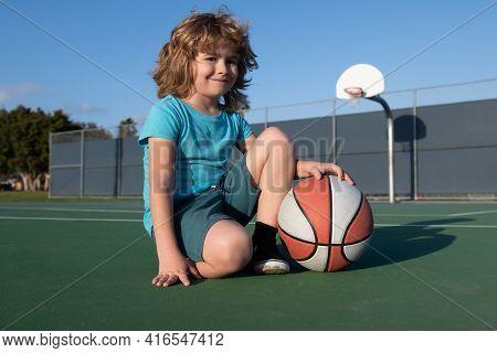 Kids Little Boy Playing Basketball. Child Sport Activity. Smiling Boy Plays Ball