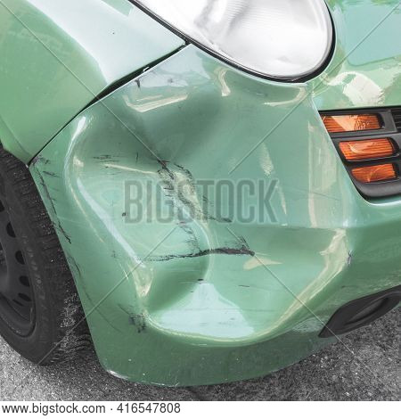 Green Dented Car. Side Body Of Car Was Damaged By Accident In Traffic. Close-up.