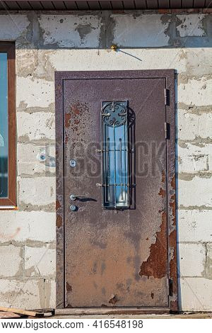 Old Rusty Iron Door In An Unfinished Abandoned House