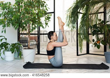 Female Yoga Teacher Practicing In Studio. Woman Doing Exercise In Bright Home