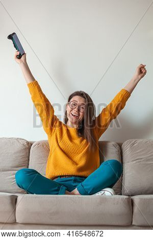 Woman Gamer Playing Mobile Phone Online Game, Winner, Holding In Hands Sitting On The Sofa