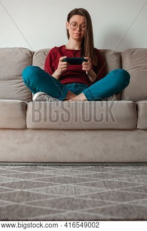 Woman Using Mobile Phone, Holding In Hands Sitting On Sofa