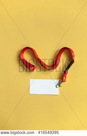 White Plastic Badge, Red Lanyard With Blank Space Mock Up Isolated On Yellow Background