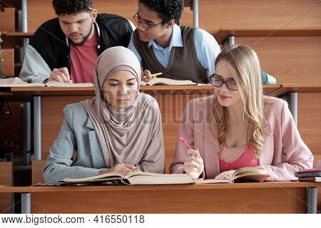 Two intercultural female students of university sitting by desk in lecture hall and looking through passage in book during group work at lesson