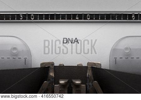 Typing text DNA on vintage manual typewriter. Close up of writes word on white paper. Shot in macro.