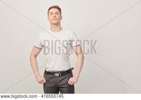 Pensive handsome man stands looking up on a white wall background. Athletic man posing at studio. Men's health.