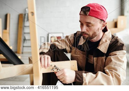 Serious young furniture assemblage specialist in workwear fixing parts of chair while assembling it in large new house, flat or studio