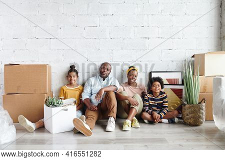 African family of father, mother and two children in casualwear sitting against white painted wall on the floor of large living-room