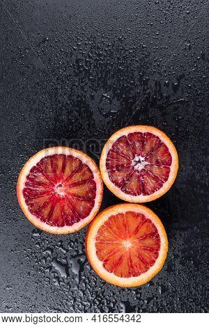 Bloody Oranges Cut In Half On Black Slate Board With Water Drops. Red Sicilian Orange Fruit. Top Vie