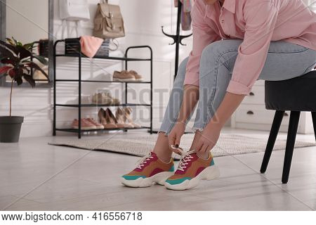 Woman Putting On Stylish Shoes In Hall Near Shelving Unit, Closeup. Space For Text