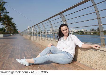 Lovely Young Woman Sitting On River Embarkment And Looking At Camera