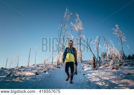 Teenager Snuggled Up In His Winter Jacket And Walks Through A Snowy Landscape In The Beskydy Mountai