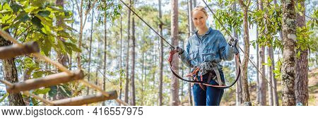 Young Brave Woman Climbing In A Adventure Rope Park Banner, Long Format