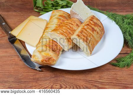 Whole And Halved Baked Sticks Made With Flaky Pastry And Cheese Filling, Separately Different Cheese