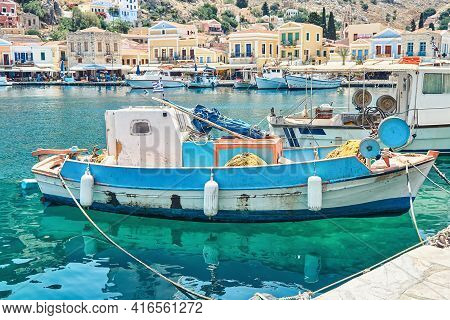 Moored Motorboats On Azure Sea With Reflection Against Historical Tourist City On Bright Summer Day