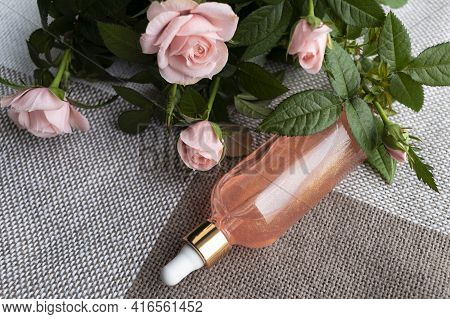 Cosmetic Serum Based On Essential Rose Oil And Roses On A Textile Background. Natural Product For De
