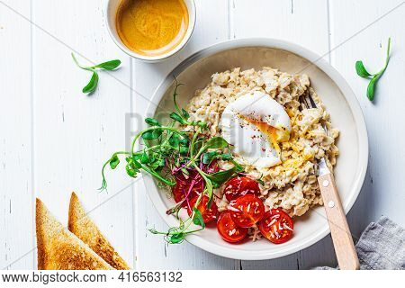 Savory Oatmeal With Poached Egg, Tomatoes, Cheese And Sprouts In A White Bowl. Healthy Breakfast Con
