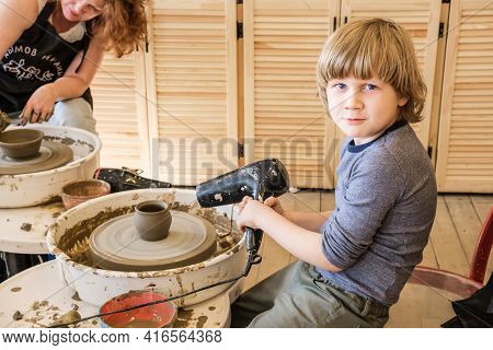 Moscow, Russia 04.11.2021 Preschooler Boy In Craft Workshop Sits In Front Of Potter's Wheel With Cla