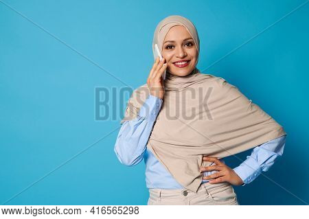Isolated Portrait Of Young Muslim Woman In Beige Hijab Talking On Mobile Phone. Confident Portrait O