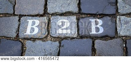 B2b Is Written On A Wet Stone Gray Wall In Big Letters. Background Image.