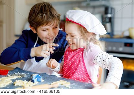 Cute Little Toddler Girl And Preteen Kid Boy Baking Easter Cookies At Home Indoors. Children, Siblin