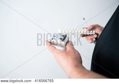 Home Repair Professional Holds Electrical Equipment In His Hands.isolated On White Background.copy S