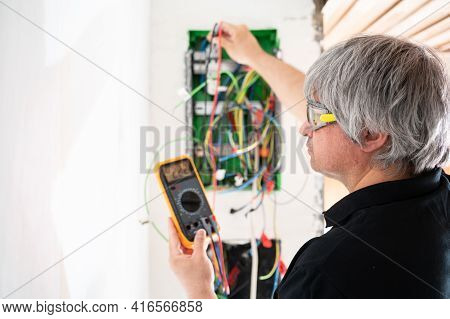 A Professional Electrician Checks The New Electrical Installation Of A House After Renovation.concep