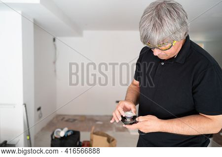 Professional Electrician Preparing New Led Bulb Lighting To Improve Home Energy Efficiency