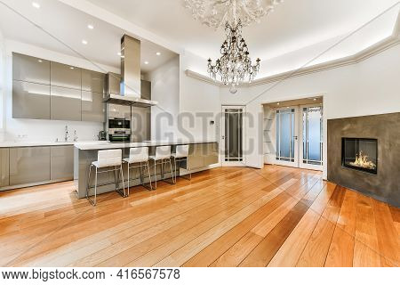 Interior Of Spacious Light Dining Room With Fireplace And Elegant Chandelier Located Near Kitchen Wi