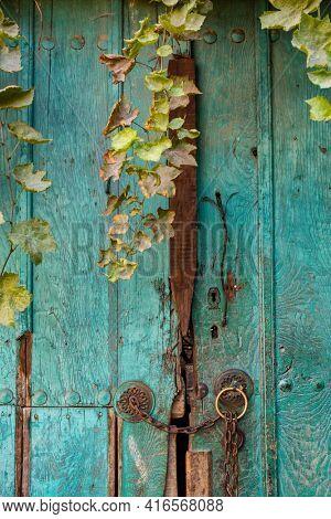 Old green wooden door of the country house. Rustic vintage door with metal chain and door handles close-up detail