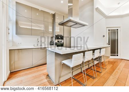Row Of Comfortable Chairs Placed Near Counters Under Exhaust Hood Against Cupboards And Oven In Cont