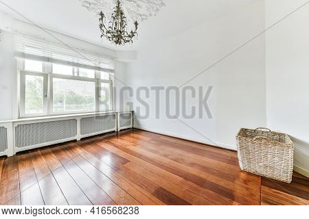 Interior Of Spacious Light Room With Electric Fireplace And Elegant Chandelier Against Balcony Door