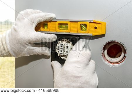 An Electrician Mounts The Black Frame Of The Roller Shutter Switch Up And Down With White Gloves In