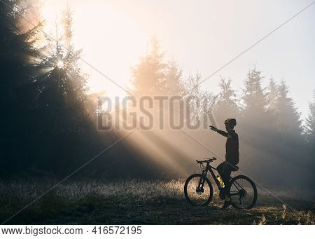 Back View Of Young Man Sitting On Bicycle And Pointing Finger At Beautiful Morning Sunlight Behind T