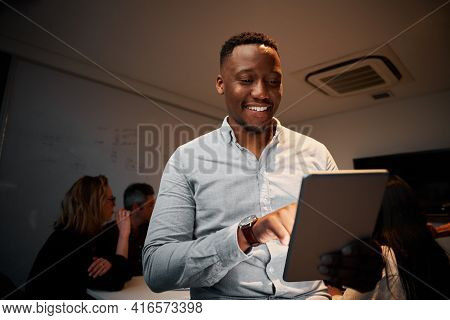 Portrait Of An Successful Young African Businessman Using His Digital Tablet In Meeting