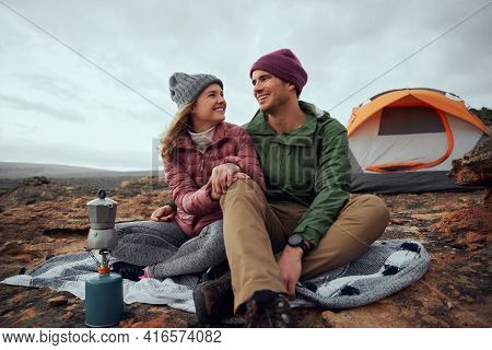 Smiling Young Man And Woman Looking At Each Other With Love And Preparing Morning Drink At Campsite
