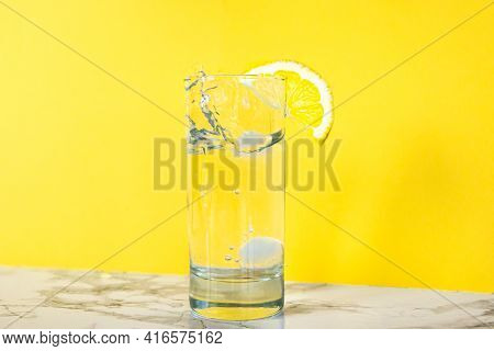 A Glass Of Clear Clear Water With Lemon. Juicy Lemon