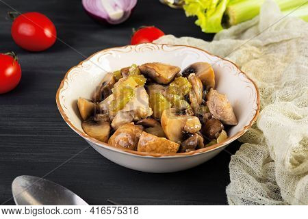 Stew Chicken Thighs With Mushrooms, Celery, Onion And Pepper. Stir Fry Chicken On Wooden Background