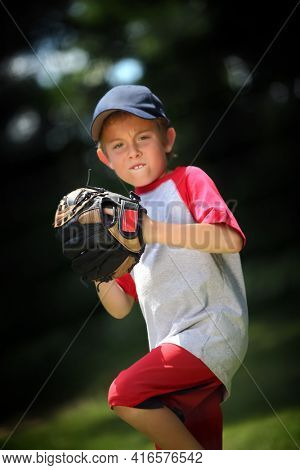 Boy practicing pitching a baseball in front of a backstop net, shallow focus on back of glove, boys face is out of focus