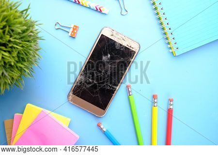 Top View Of Broken Smart Phone And Stationary On Color Background